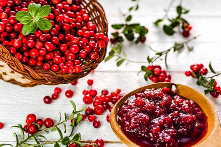 Red berry jam in a bowl on white table, natural organic product - homemade preserve for winter Stock Photo