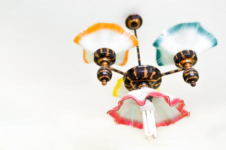 Retro kroonluchter met energiezuinige lamp die onder plafond hangt Stockfoto - 87929485
