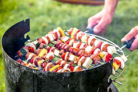 Skewers on barbecue grill in the garden, man preparing shashlik with vegetables and meat, grilling food, outdoor party in the summer garden