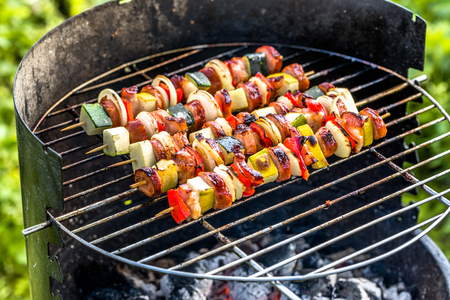 Spicy vegetables and meat kebabs grilled over the coals on barbecue grill, food grilling outdoor in the summertime