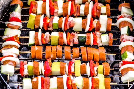 Grilling food on barbecue grill, skewers with meat and vegetables, outdoor bbq, grid with colorful shashliks, close-up