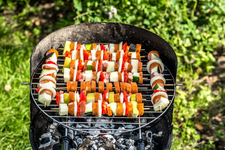 Shashliks on barbecue grill on grass, skewers with meat and vegetables, grilling food, outdoor bbq in the summer garden
