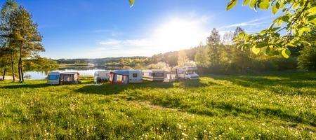 家族旅行の概念。キャラバンと湖でキャンプします。