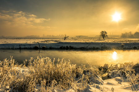 snowy field: Winter river landscape, moody scenery with morning sun reflection in the water Stock Photo