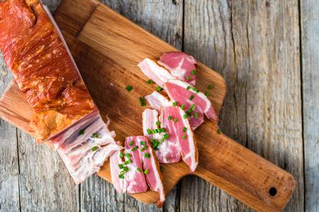 Gerookt spek op houten tafel, varkensvlees Stockfoto - 88485172