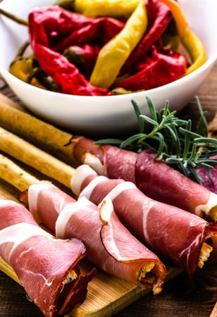 Bread with prosciutto or grissini stick with ham, traditional italian antipasti, food platter