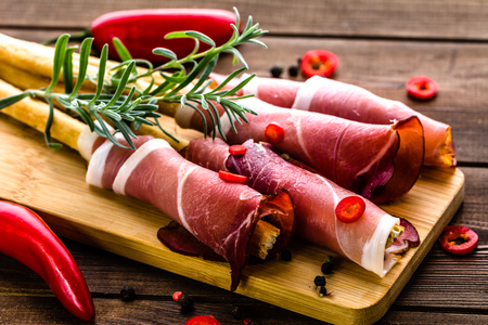 Sticks of bread with prosciutto, italian antipasto, food platter with meat, cold appetizer on wooden table Stock Photo