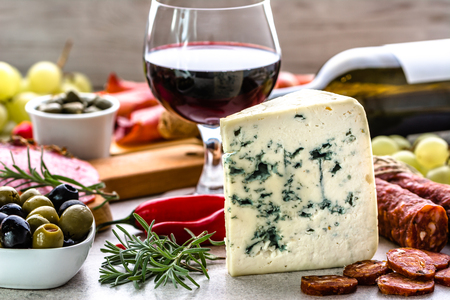 caper: Blue cheese and wine snack set, italian antipasto or spanish tapas bar, selection of food on table in restaurant