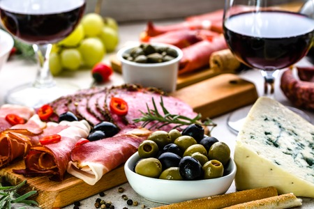 Variety food on table, wine snack set, olives, cheese and other appetizer, italian antipasti on plate