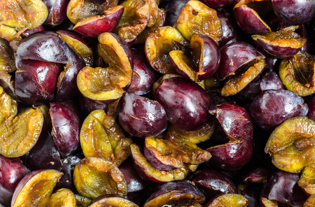 Pitted prune plums background, natural texture