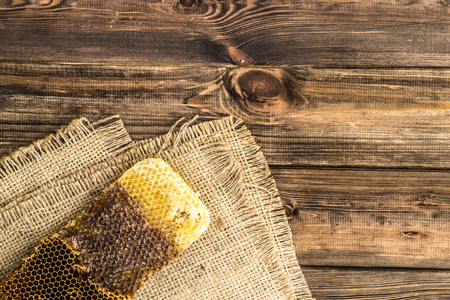 Honeycombs with honey on rustic wood background covered with jute sackcloth, top view.