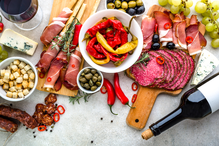 Spicy tapas on table, food from spain, variety dishes, cold meat and wine, top view