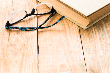 茶色の木製の板の背景に古い本と眼鏡