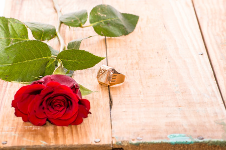 Red roses and engagement ring on wooden background, wedding invitation concept Stock Photo
