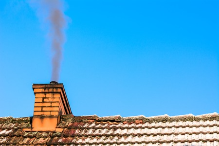 Old house with chimney smoke, air pollution and smog in winter, ecological issues