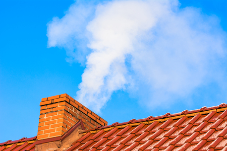 Modern house roof with chimney smoke, air pollution and smog in winter, ecological problems