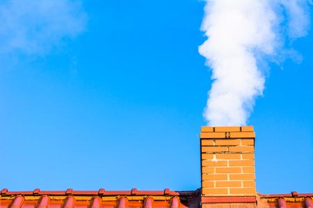 Nowoczesny dach domu z dymem kominowym, zanieczyszczeniem powietrza i smogiem zimą, problemy ekologiczne