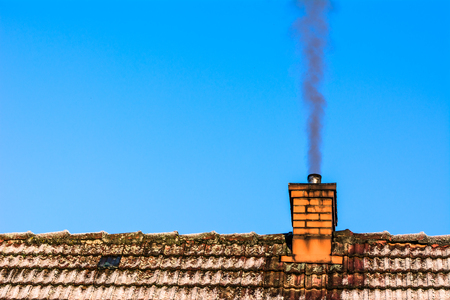 Old house roof with chimney smoke, air pollution and smog in winter, ecological problems