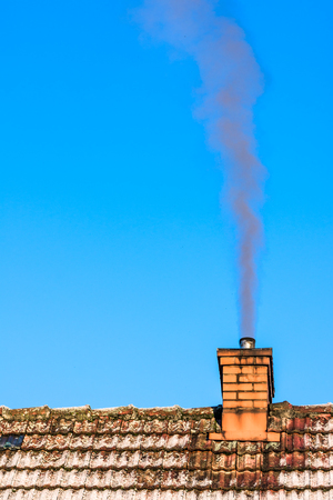 Old roof of house with chimney smoke in air, environment pollution and smog in winter, ecological problems Stock Photo