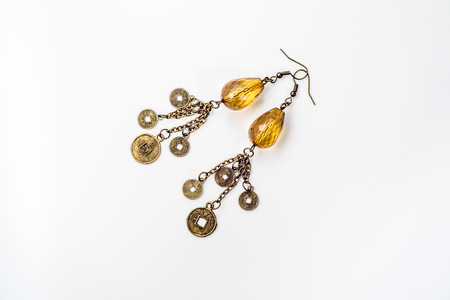 Handmade earrings jewelry made with antique gold and amber isolated on white background Stock Photo