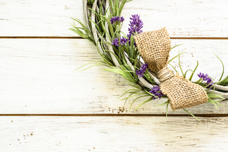 Braided wicker wreath with lavender flowers on vintage wood background. Provencal style. Stock Photo
