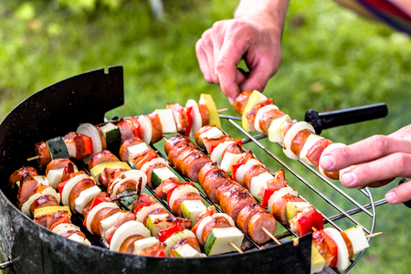 Grilling food on barbecue grill, hands preparing skewers with vegetables and sausage, bbq on grass, outside summer party concept Stock Photo