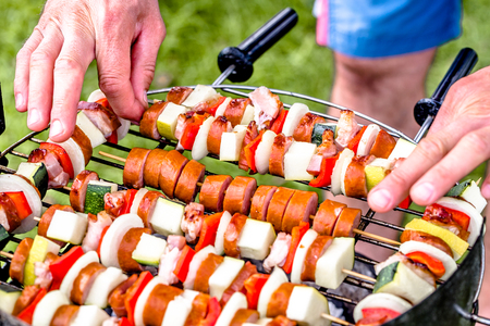 Grilling food on barbecue grill, hands preparing skewers with vegetables and sausage, bbq on grass