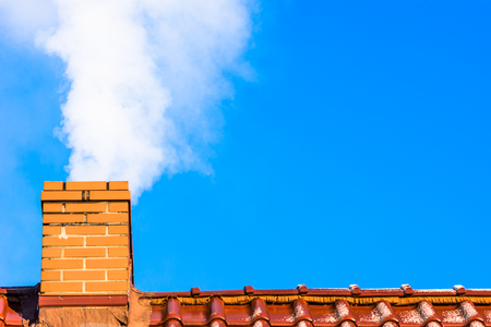 Modern house roof with chimney smoke