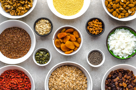 Vegetarian breakfast with healthy food selection, dry fruits, cereals, nuts, seeds, goji berries and other superfoods on table, flat lay, overhead