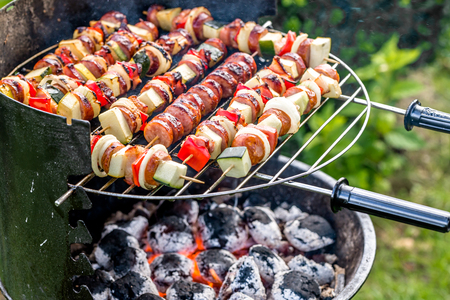 Vegetables and meat skewers on barbecue grill with hot food, grilling outdoor in the summer backyard