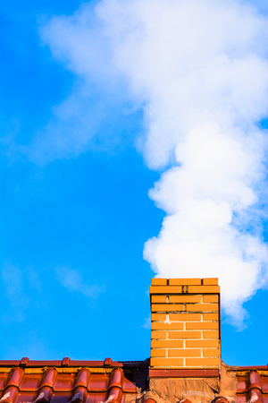 Modern house roof with chimney smoke, air pollution by co2 emission, reason of smog in winter