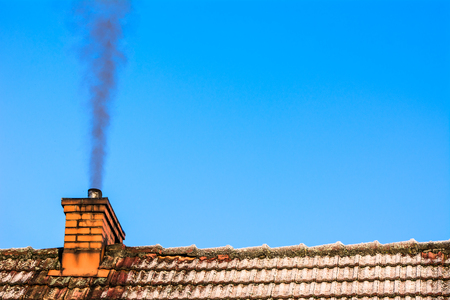 Old house roof with chimney smoke, air pollution by co2 emission, reason of smog in winter