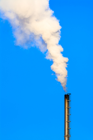 Power plant smokestack with carbon emission - co2, dioxide or fossil fuel. Air pollution by industry. Chimney and smoke cloud on blue sky background. Stock Photo