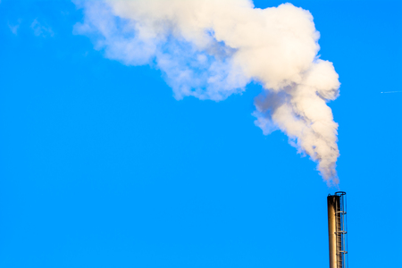 Power plant smokestack with carbon emission - co2, dioxide or fossil fuel. Air pollution by industry. Chimney and smoke cloud on blue sky background. Reklamní fotografie