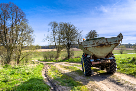 Tractor on farm land road driving to the field, agricultural landscape in spring 스톡 콘텐츠