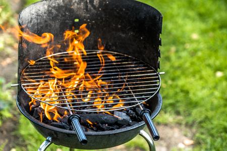 庭でグリルするための火、木炭とグリッドとバーベキューグリル、草の上の夏のピクニック、屋外