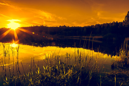 Nature landscape with sunset sky and sun reflection in the water of calm lake