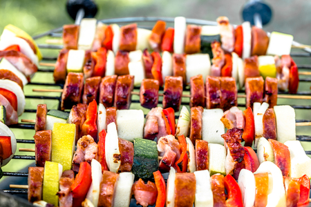 Grilling skewers with vegetables and sausage on barbecue grill, outdoor bbq with colorful grilled food, closeup