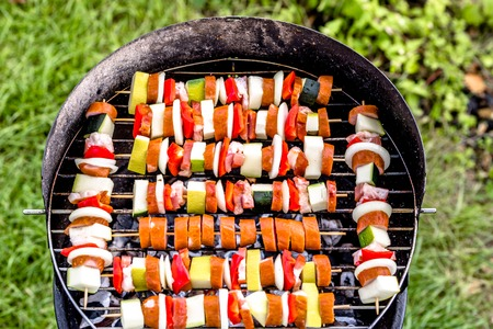 Grilling food on barbecue grill, skewers with vegetables and sausage, grilled food with outdoor bbq in the garden