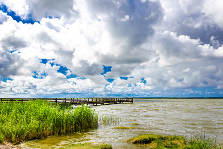 Molo over lake, landscape with spring green area of grass over water and sky with horizon