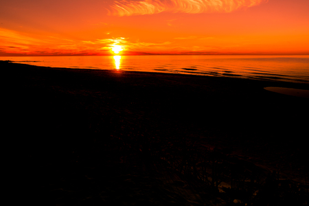 Silhouette of sunset beach, landscape of sky with red sun going in to the sea Stock Photo