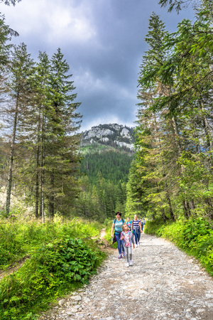 ZAKOPANE, POLAND - AUGUST 16, 2016: Tour with hikers on hiking trail, trekking in Tatra Mountains, travel and tourist background