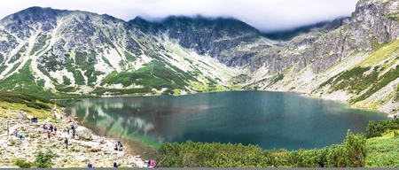 ZAKOPANE, POLAND - AUGUST 16, 2016: Group of hikers over lake in mountains, travel destination of tourist trip in the summer, Czarny Staw Gasienicowy, High Tatra Mountains Editorial