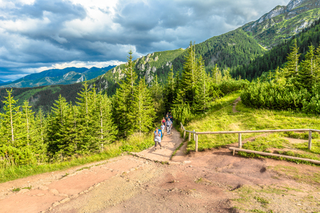 ZAKOPANE, POLAND - AUGUST 14, 2016: Group of hikers on hiking trail in mountains, trekking in Tatra Mountains, summer landscape, Poland