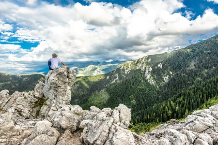 ZAKOPANE, POLAND - AUGUST 14, 2016: Young guy hiker on the top of mountain rock, panoramic vista of mountains, succes concept