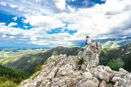 ZAKOPANE, POLAND - AUGUST 14, 2016: Young hiker on the top of mountain rock, panoramic vista of mountains, succes concept