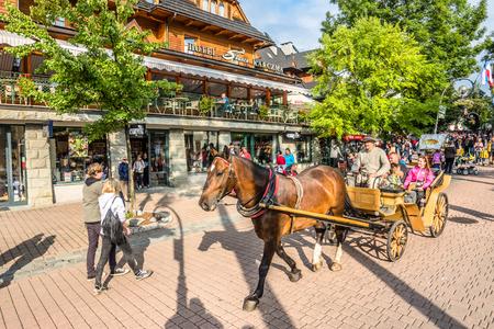 ZAKOPANE, POLAND - AUGUST 17, 2016: Promenade of city center in Zakopane, People tourists enjoy carriage ride through Krupowki street in the summer season Sajtókép