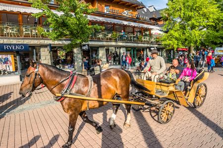 ZAKOPANE, POLAND - AUGUST 17, 2016: Promenade of Zakopane, tourists on a carriage ride through Krupowki street in the summer vacation, touristic attractions Sajtókép