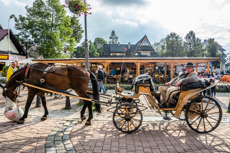 ZAKOPANE, POLAND - AUGUST 17, 2016: Touristic season in Zakopane, city center. Coachman with harnessed horse on the Krupowki street waiting for tourist Sajtókép