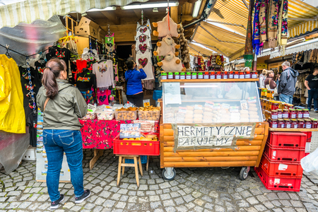 ZAKOPANE, POLAND - AUGUST 17, 2016: Street trading in the city center of Zakopane - sale of tourist souvenirs - people buying homemade regional product and handicraft